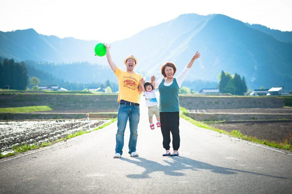 青い山並みの前で手を挙げる家族の写真