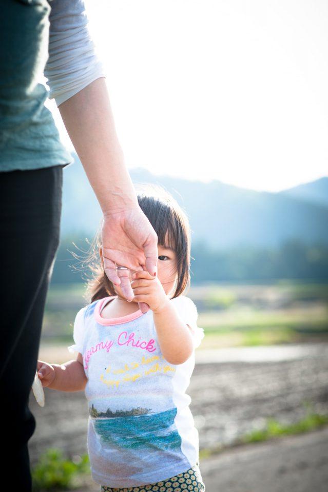 親と手を繋ぐ子どもの写真