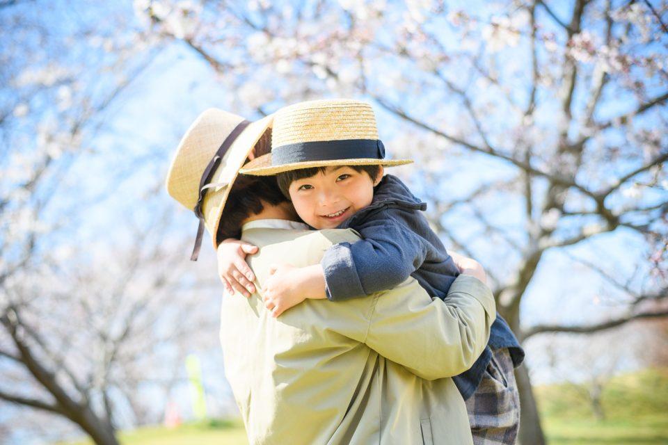 お客様の声をいただいた写真の一例(桜並木の前で母に抱きかかえられる子)