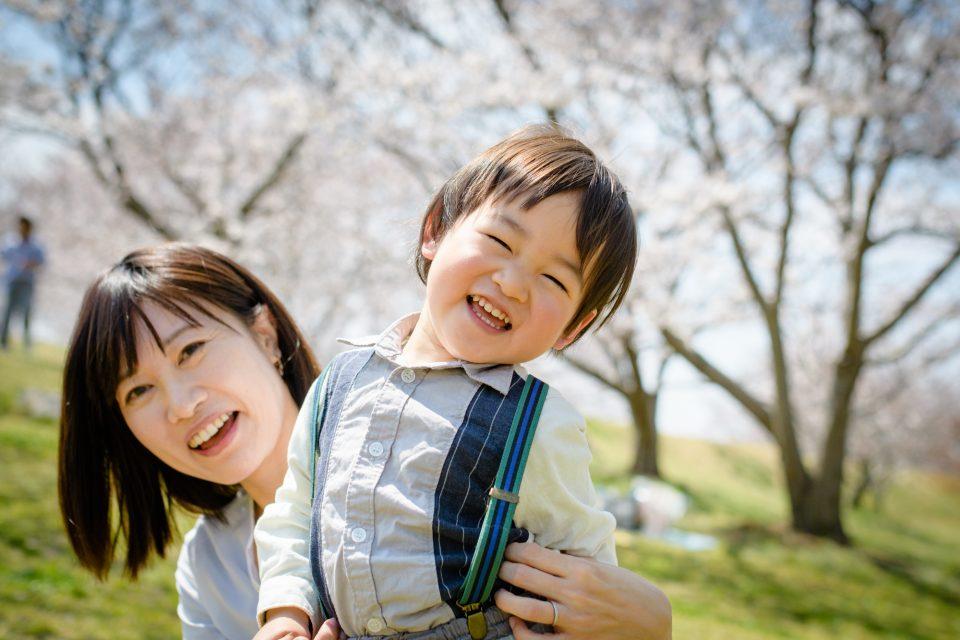 お客様の声をいただいた写真の一例(桜並木の前で笑顔の母子)