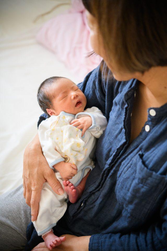 お母さんに抱っこされた新生児