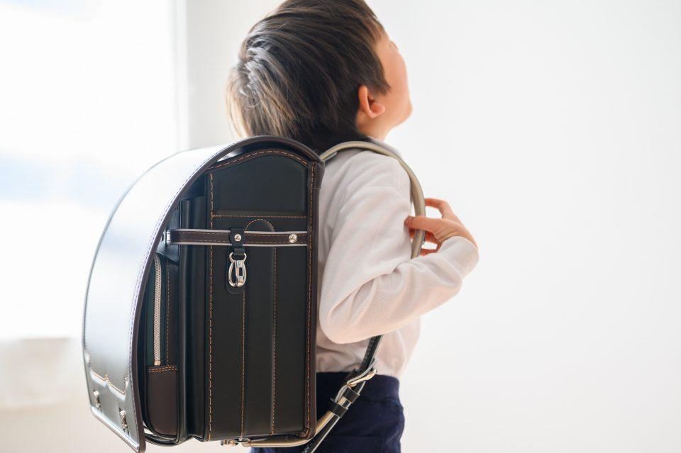 一年生が黒いランドセルを背負っている後ろ姿